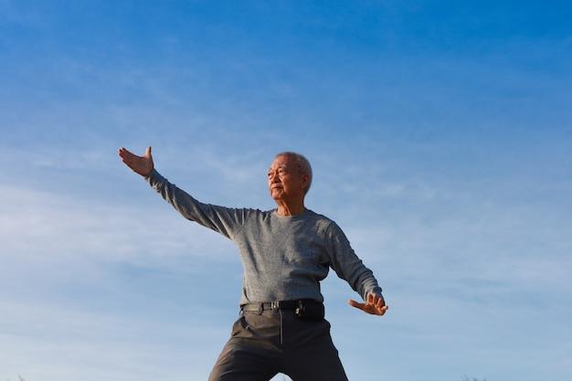 Anciano mayor asiático practicar taichi kungfu chino en la playa