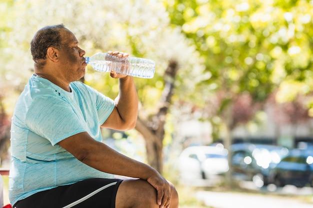 Un anciano negro con sobrepeso y obesidad mórbida está bebiendo agua en el parque