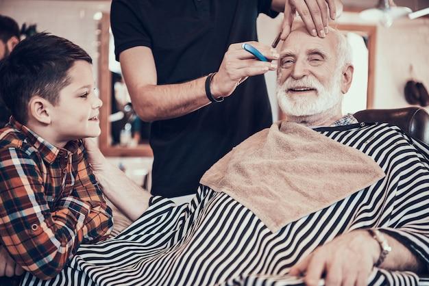 Anciano con niño en la barbería juntos.
