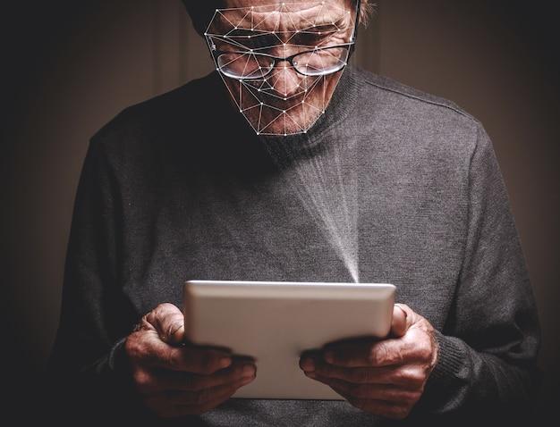 Anciano con nuevo teléfono inteligente con tecnología de identificación facial