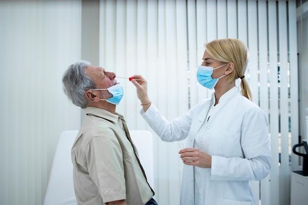 Anciano obteniendo una prueba de pcr en el consultorio médico durante la epidemia de covic19