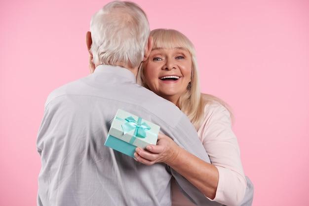 Anciano en pajarita presenta caja de regalo a anciana