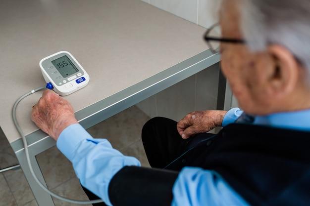 Anciano de pelo blanco con gafas sentado delante de una mesa de la cocina comprobando su medición de la presión arterial