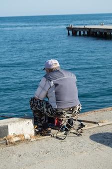 Un anciano pescador sentado en un parapeto junto al mar y pescando en una caña de pescar