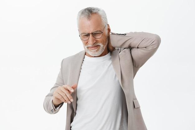 Anciano preocupado en traje quejándose de dolor de espalda, tocando el cuello
