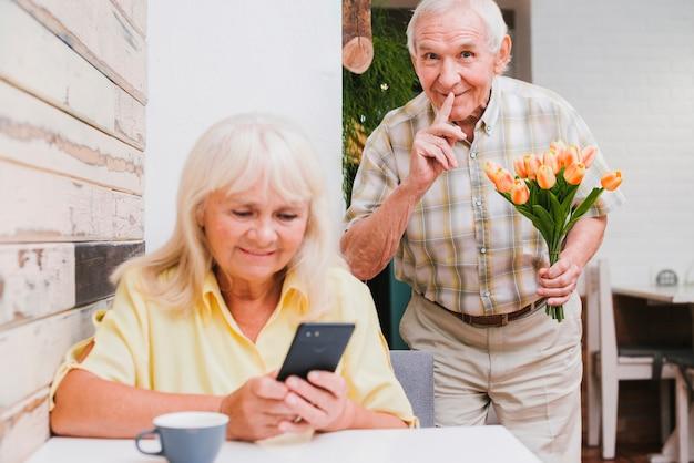 Anciano preparando sorpresa con bouquet para esposa