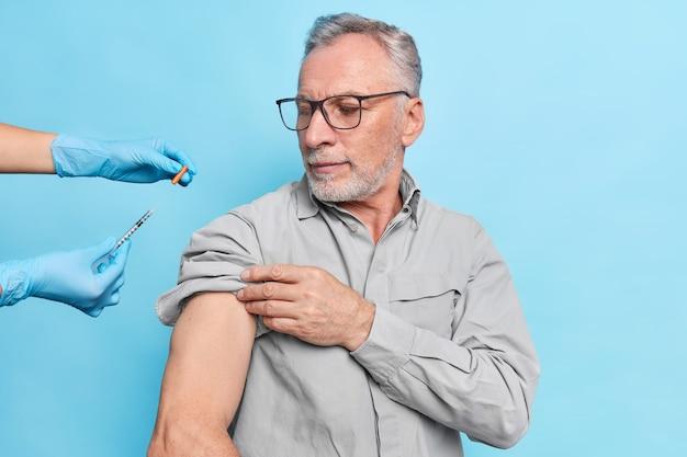 Anciano recibe vacunación contra coronavirus mira atentamente jeringa con vacuna usa anteojos
