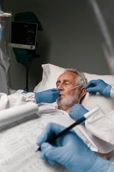 Anciano con respirador junto a médicos