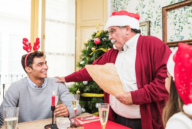 Anciano en rojo leyendo de papel en mesa festiva