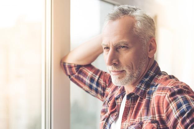 Anciano en ropa casual está mirando por la ventana.