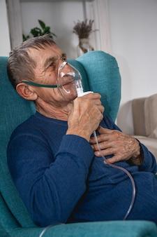 Anciano senior se sienta en un sillón con una máscara de oxígeno en cuarentena