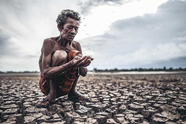 Un anciano sentado en contacto con la lluvia en la estación seca, el calentamiento global, el enfoque de selección