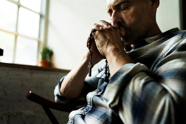 Anciano sentado orando pensativo