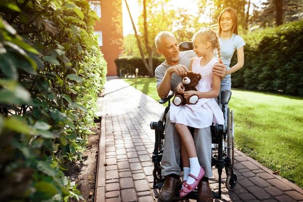 Un anciano está sentado en una silla de ruedas.