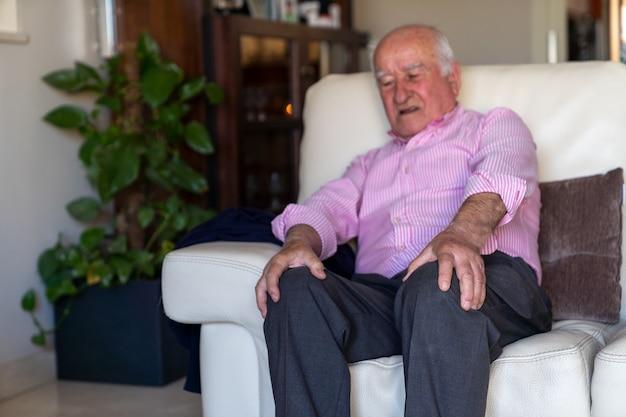 Anciano sentado en un sofá sintiendo dolor y dolor en las rodillas