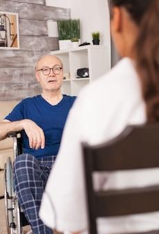 Anciano en silla de ruedas hablando con la enfermera sobre su problema médico.