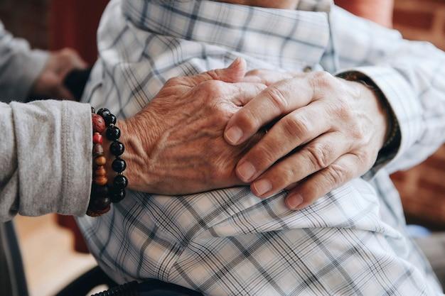 Anciano en silla de ruedas sosteniendo la mano de su esposa sobre su hombro