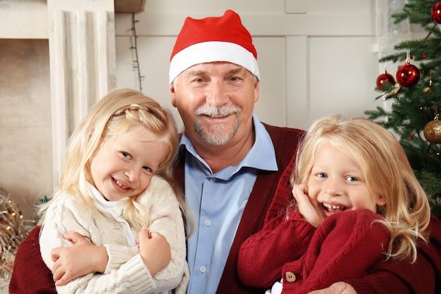 Anciano con sombrero de navidad con nietos en casa