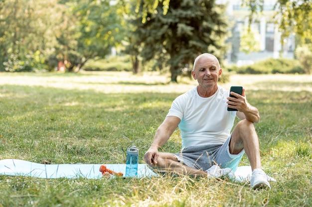 Anciano sonriente checando su teléfono con colchoneta de yoga