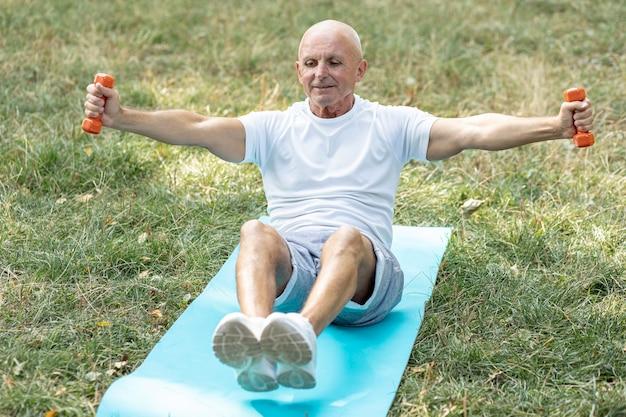 Anciano sonriente trabajando en estera de yoga