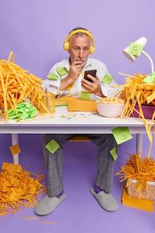 Un anciano sorprendido lee noticias impactantes en internet a través de un teléfono inteligente, busca nuevas canciones para su propio blog musical en las redes sociales, posa en el escritorio, hace una lista de tareas en las pegatinas