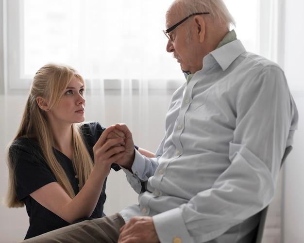 Anciano sosteniendo la mano de la enfermera