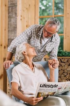 Un anciano sosteniendo la mano de su esposa sentada en una silla con periódico