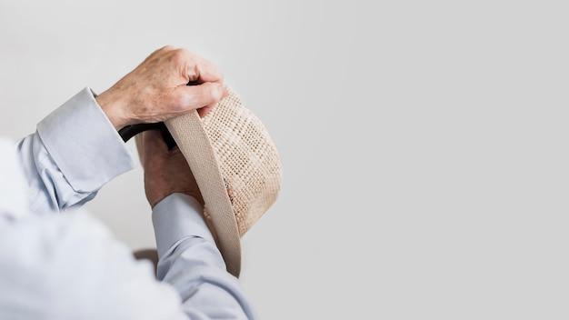 Anciano sosteniendo sombrero y bastón con espacio de copia
