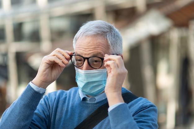 Anciano sosteniendo sus anteojos empañados debido a la máscara, concepto de visión de coronavirus covid