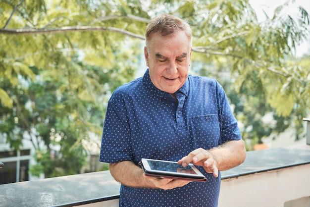 Anciano con tableta digital
