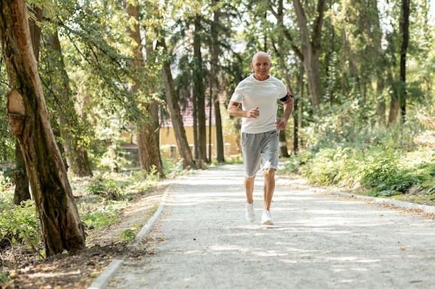 Anciano de tiro completo corriendo en el bosque