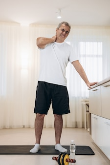 Anciano tocando los músculos de la espalda superior y sintiendo dolor