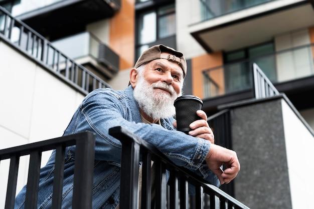 Anciano tomando una taza de café al aire libre en la ciudad