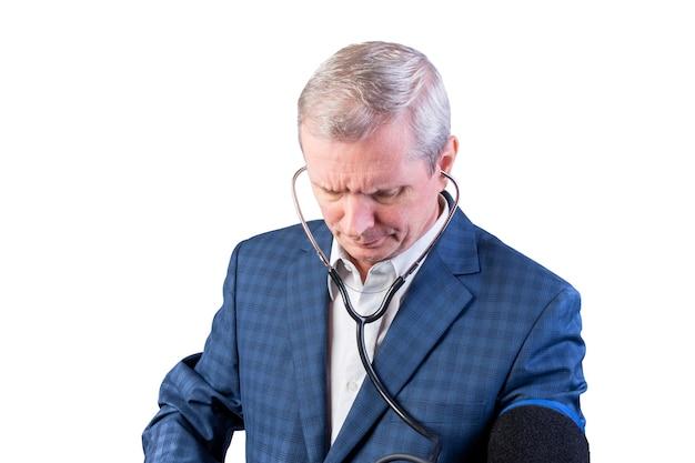 Un anciano con traje mide la presión, él mismo, con un tonómetro de mano. aislado en un fondo blanco. para cualquier propósito.