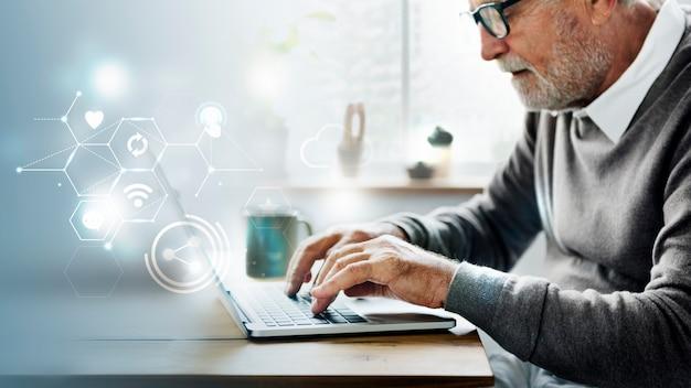 Anciano usando una computadora portátil