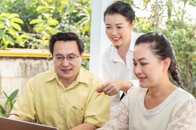 Ancianos amigos asiáticos mirando portátil pantalla en hogar de ancianos.