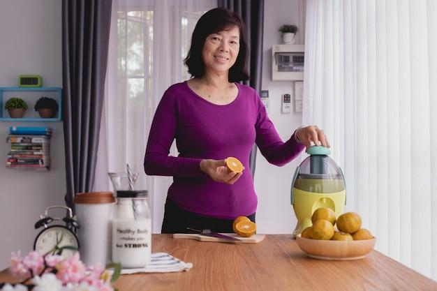 Ancianos asiáticos sonrientes hacen jugo de naranja por licuadora.