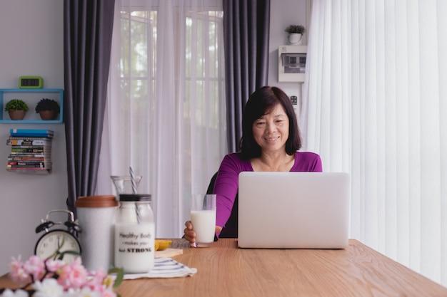 Ancianos asiáticos usando laptop y bebiendo leche en casa.