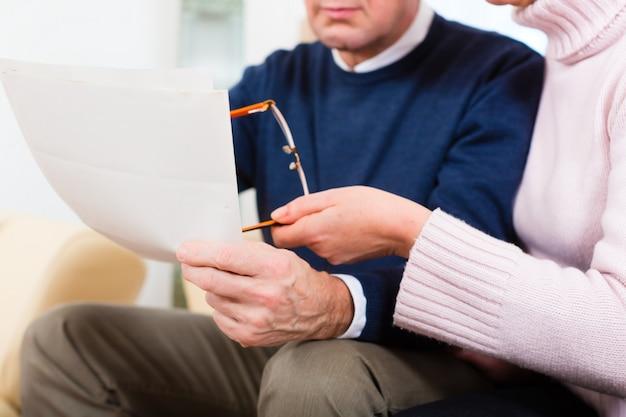 Ancianos en casa recibiendo carta de estar molesto