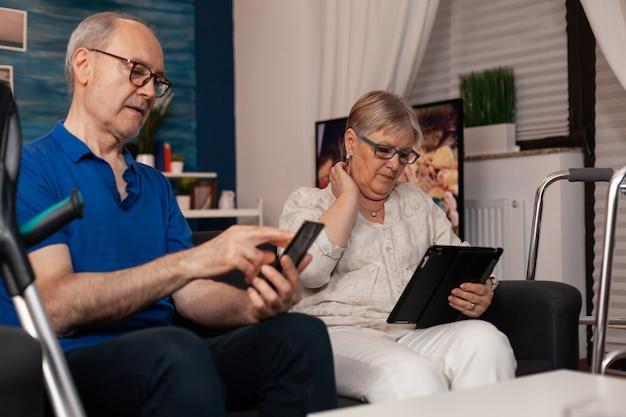 Ancianos casados usando dispositivos digitales y sentados juntos