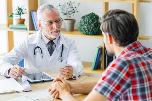 Ancianos doctor escuchando paciente joven
