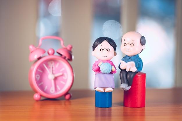 Ancianos en miniatura, abuelo y abuela sentados en el fondo del reloj rosa usando como concepto de familia y seguro