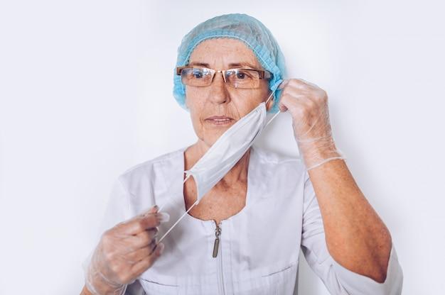 Ancianos tristes cansados mujer madura médico o enfermera en una bata blanca médica, guantes, se pone la mascarilla usando equipo de protección personal aislado. concepto de salud y medicina. pandemia de covid-19