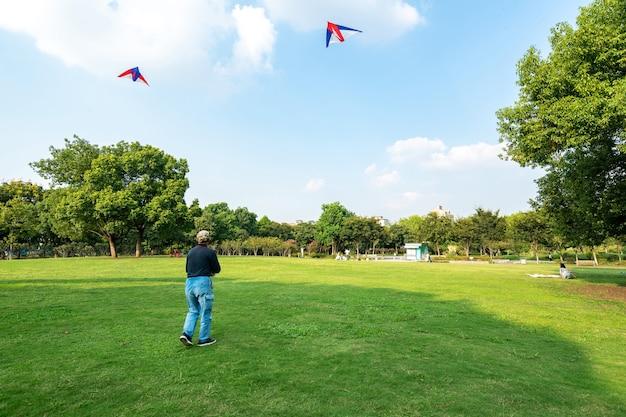 Ancianos volando cometas en el césped del parque de ocio