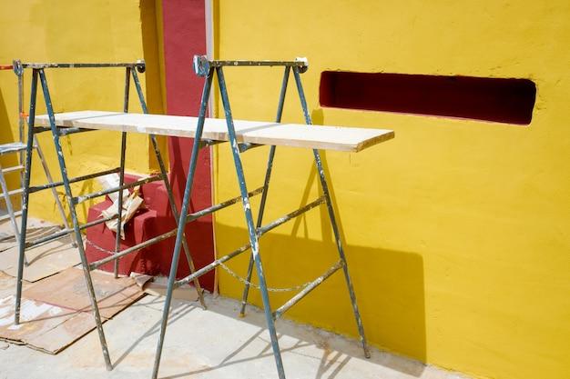 Andamio en el suelo utilizado para repintar las paredes exteriores de una casa durante el verano con pintura amarilla al estilo tradicional mexicano.