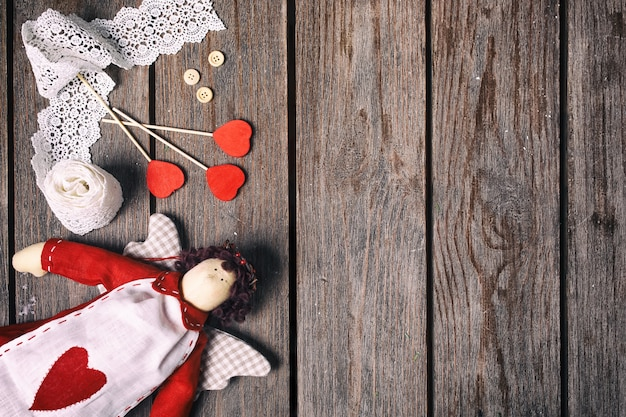 Angel un peluche con corazón, cinta de encaje, botones y tres corazones rojos sobre fondo de madera vieja. concepto de san valentín. vista superior.