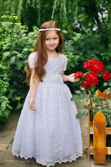 Angelito cristiano. recién bautizado adorable niña armenia pelirroja sosteniendo una rosa roja en el jardín