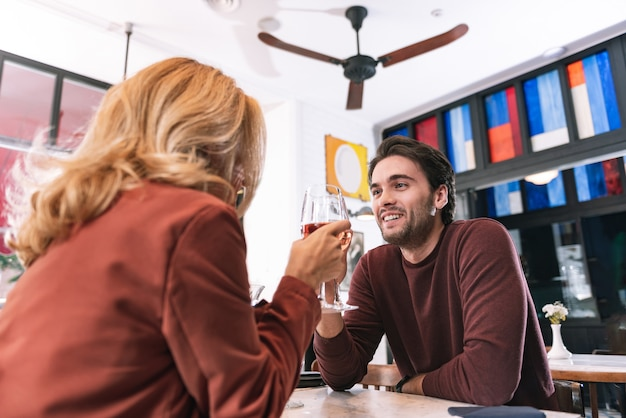 Ángulo bajo de agradable pareja positiva bebiendo vino y hablando