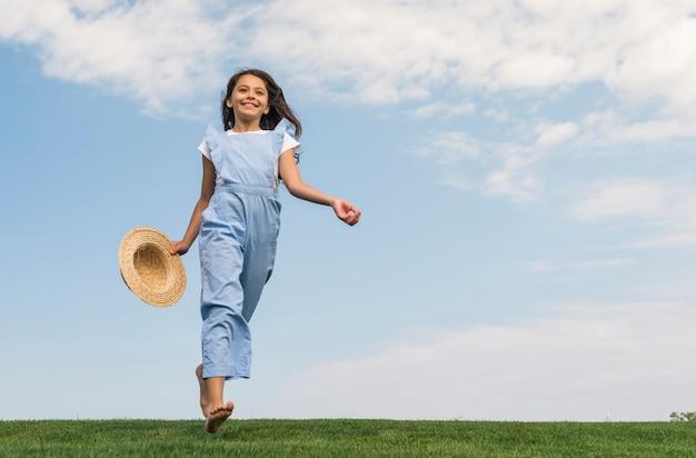 Ángulo bajo alegre niña corriendo sobre hierba