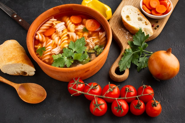 Ángulo alto brócoli zanahorias y fusilli en un tazón con pan en la tabla de cortar y cuchara de madera